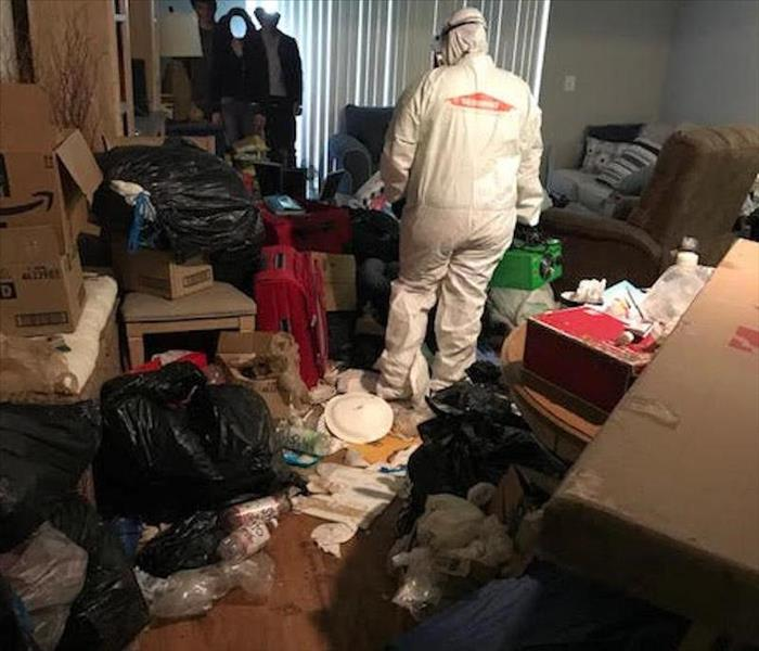 SERVPRO employee standing in a room filled with trash.