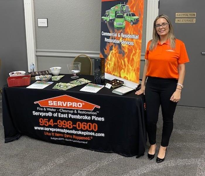 A female SERVPRO employee standing in front of a table.