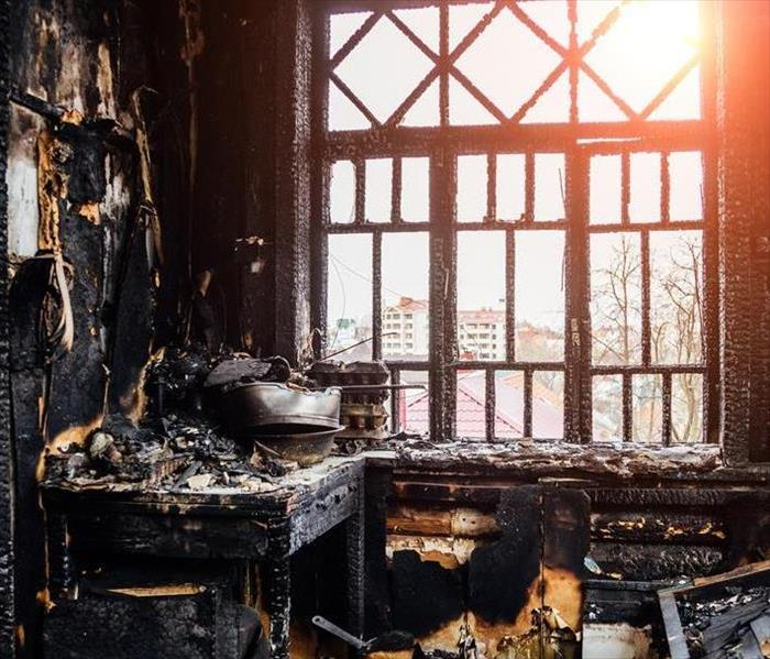 A room with fire and soot damage that has a window overlooking a city.