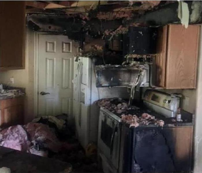 A kitchen covered in soot and smoke damage after a fire