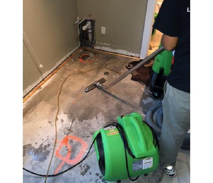 SERVPRO tech removing water from water damaged floor