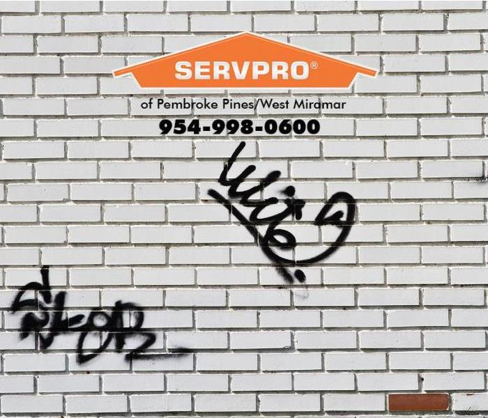 The outside wall of a business has been vandalized by graffiti spray painted on the wall.