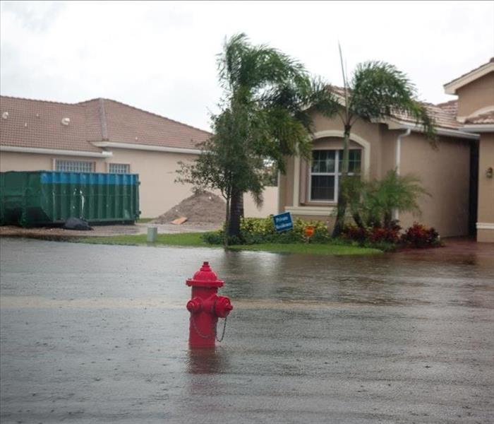Two houses in a neighborhood surrounded by water from a storm.